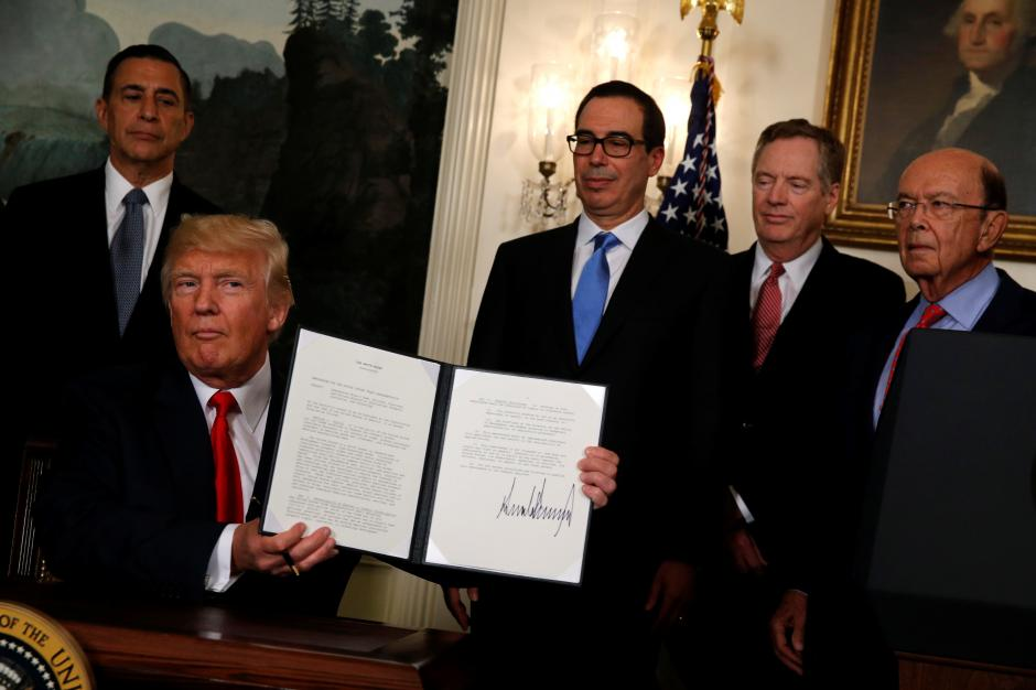U.S. President Donald Trump, flanked by U.S. Representative Darrell Issa (R-CA) (L), Treasury Secretary Steven Mnuchin (3rd R), U.S. Trade Representative Robert Lighthizer (2nd R) and Commerce Secretary Wilbur Ross (R), finishes signing a memorandum directing the U.S. Trade Representative to complete a review of trade issues with China at the White House in Washington, U.S. August 14, 2017. REUTERS/Jonathan Ernst